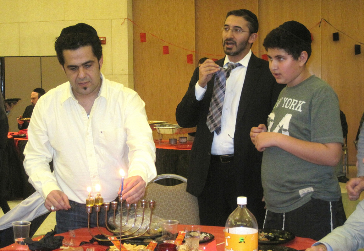 Sol Benshabbat lights Chanukah candles in memory of his father during the Sephardic Torah Center of Dallas' first-day celebration Dec. 9. More than 300 people attended the event at Ann and Nate Levine Academy's social hall, which featured a juggler, crafts for children and a kosher Chinese meal.|Photo: Courtesy Sephardic Torah Center of Dallas