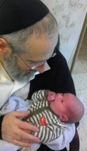 Rabbi Yerachmiel Fried with his first grandson, Eliyahu Gross, during his bris in Israel. | Photo: Courtesy Rabbi Yerachmiel Fried