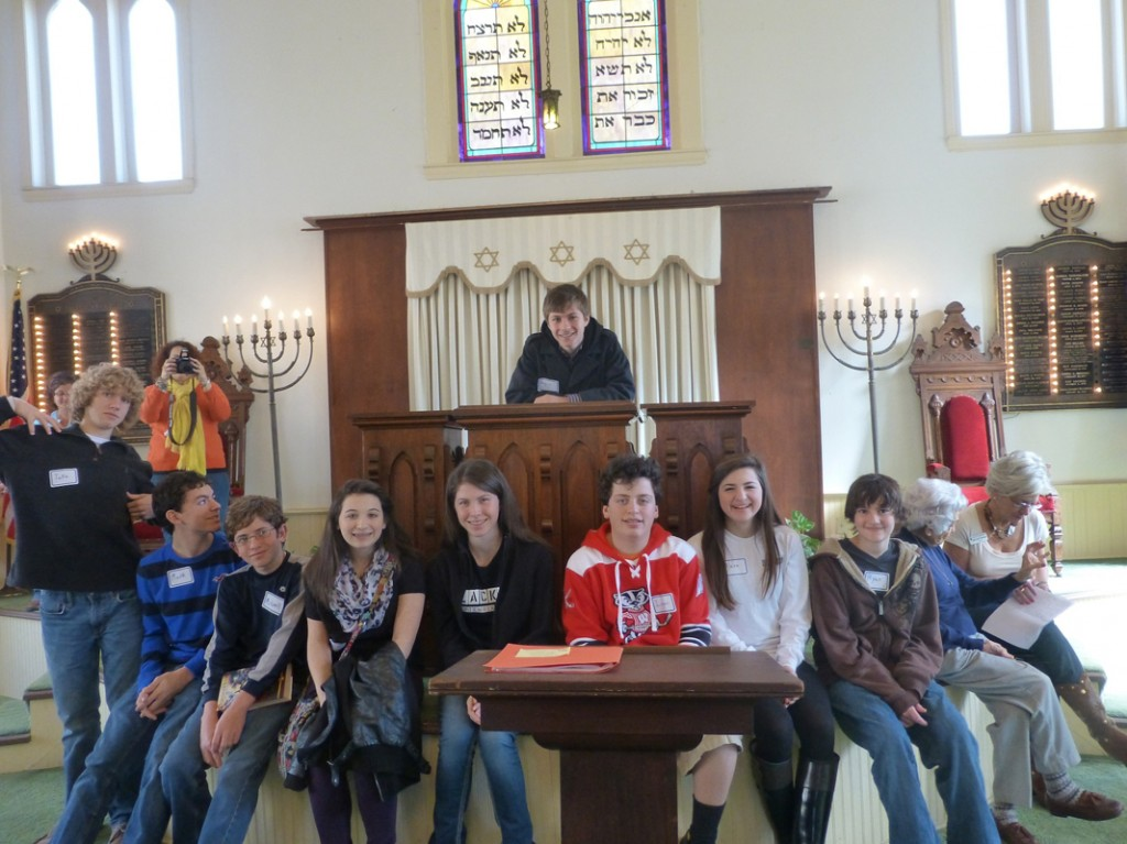 Beth-El Congregation students visited Temple Beth El in Corsicana to learn about this history of Texas Jews. Attendees included, seated from left, students Jake Hyman, Mark Mowry, Mitchell Gorsd, Avery Simon, Megan Kalpin, Isaac Narrett, Alexa Sankary and Ryan Goldstein, and speakers Babette Samuels of Corsicana and Hollace Weiner, Beth-El historian. Student Bryce Kleinman is standing on the bimah. | Photo: Ilana Knust