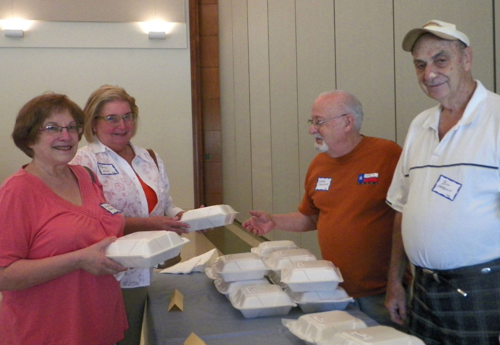 Karen Ferstenfeld and Patty Klint are served their lunches by Larry Steckler and Bill Margolis.
