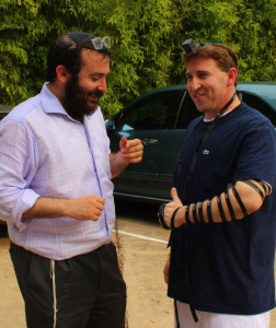 Rabbi Zvi Drizin helps Matthew Prescott lay tefillin as a way to honor the security of Israel.