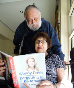"Dr. Julian Haber peers over his wife Marian's shoulder as they check out the part in Wendy Davis' book ""Forgetting to be Afraid,"" that mentions Davis' employment in the front office of his pediatric office with Dr. Barry Bzostek. 