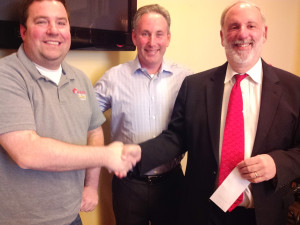 From left, Brad Schweig and Mark Lowey present a check from Jewish Business Alliance to JFS CEO Michael Fleisher.