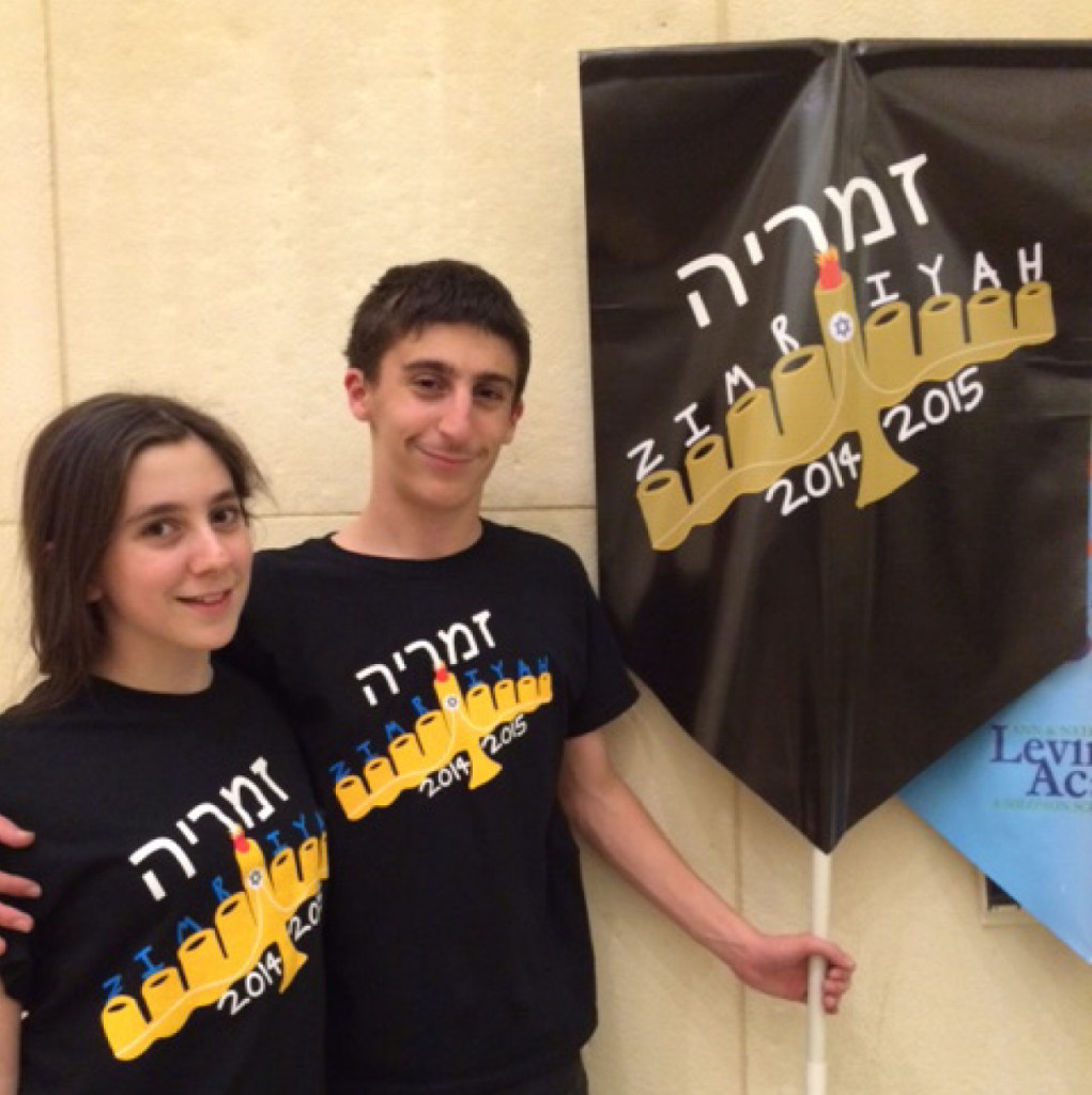 Saul Zimmerman poses with his sister Molly next to the logo he designed for Levine Academy's annual Zimriyah evening of song. Saul was recently named to the American Hebrew Academy Honor Society.