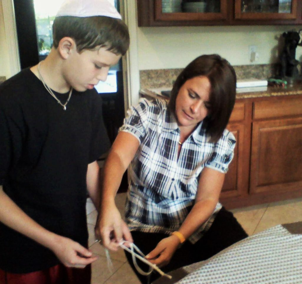 Wende Weinberg's impact in the community comes from her roles at Levine Academy, Anshai Torah and touching students – one to one — here in 2010, helping Jonah Silverthorn learn to tie the knots — in fact, tying him forever to Jewish tradition — as together they created his own tallit.
