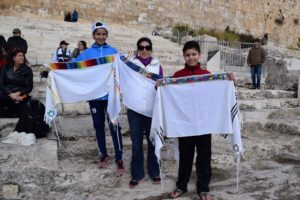 Photo: Adam Kaplan Irene Sibaja (center) and her children Tova (left) and Sam at the Ohpel ruins at the Temple Mount. They received their tallitot for the children's b'nai mitzvah.
