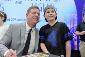 Former Cowboys quarterback and NFL commentator Troy Aikman takes a photo with Zachary Goldminz, who was diagnosed with Ewing Sarcoma two years ago.