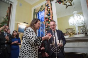 Cecilia Abbott and Trevor Pearlman light the menorah at the governor's Hanukkah party Dec. 17.