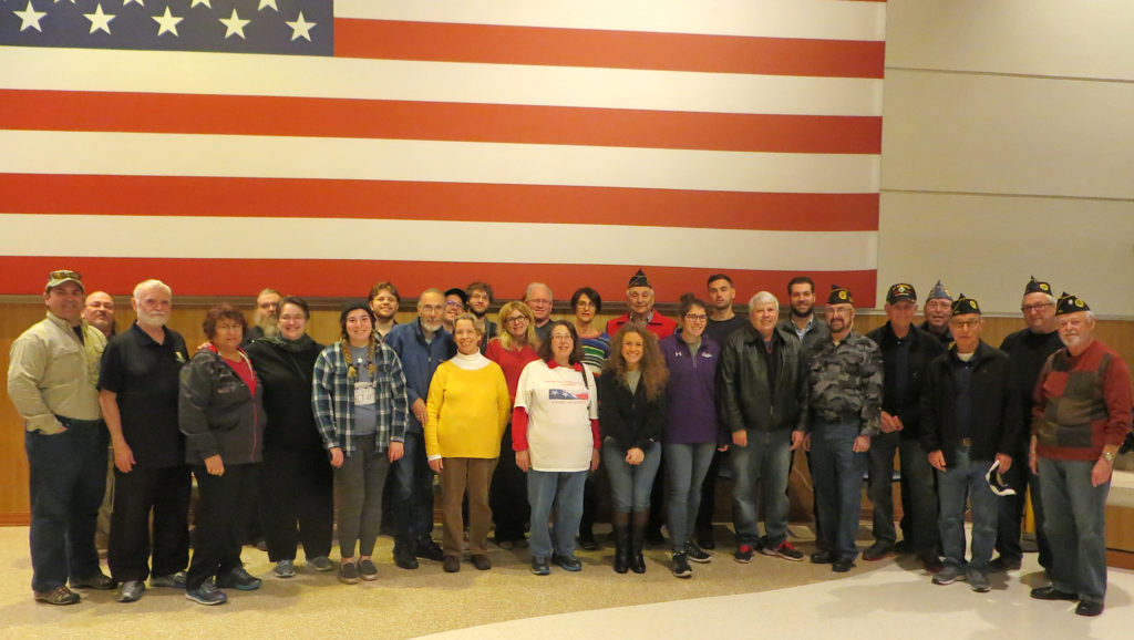 Photo: Steve Krant JWV and JWV Auxiliary volunteers posed beneath the large American flag in the VA's atrium after a job well done! The JWV Post 256 assembled and delivered more than 200 gift bags to patients at the VA on Christmas Day.